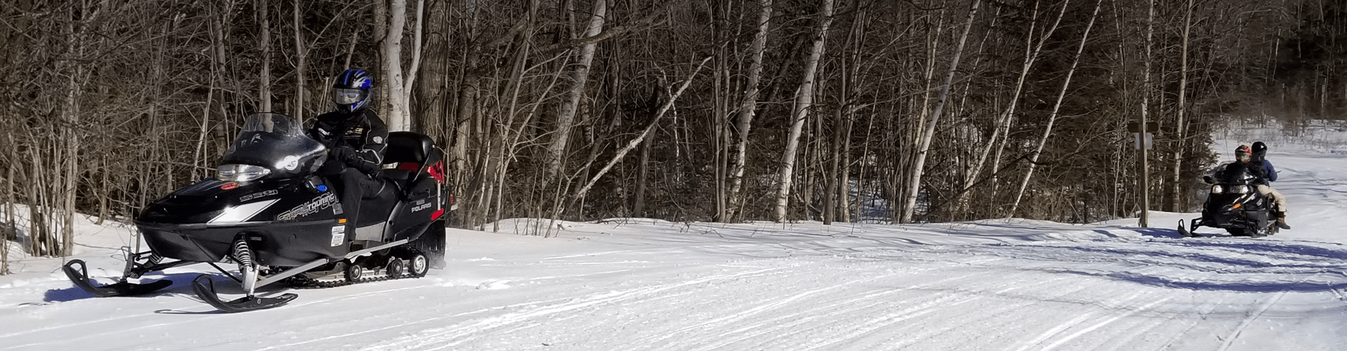 Snowmobiling on a trail in Northern NH